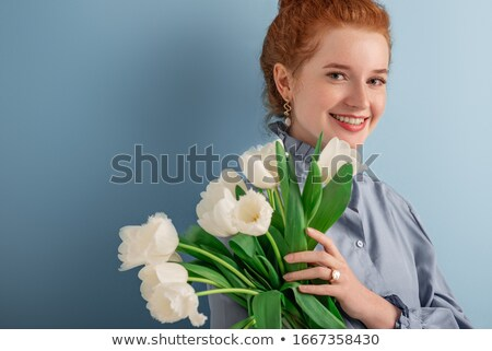 close up portrait of a redheaded woman holding tulip flowers stock photo © deandrobot