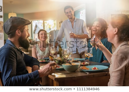 man mixing vegetable salad and having dinner with friends stock photo © deandrobot