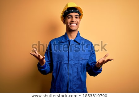 Young builder with arm out in a welcoming gesture. Stock photo © RAStudio