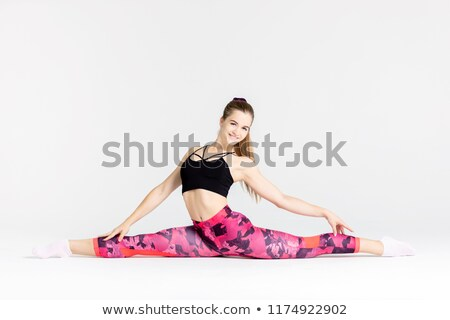 Full length portrait of a young flexible sportwoman Stock photo © deandrobot