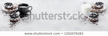 glass of milk and doughnuts with black cookies on stone kitchen table background space for text to stock photo © denismart
