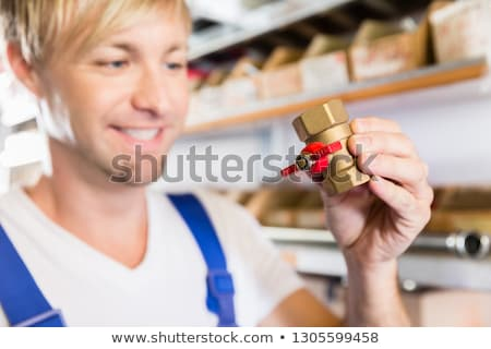 Hands of a worker holding two pipe fitting accessories in a sanitary shop Stock photo © Kzenon