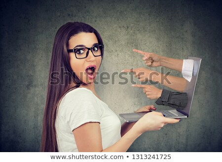 shocked woman holding laptop being picked blamed by many people in the Internet Stock photo © ichiosea