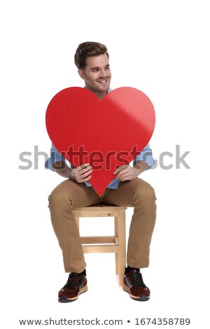 man holding a red heart on hand while looking away Stock photo © feedough