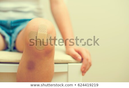 Stock photo: Girl Knee With An Adhesive Bandage