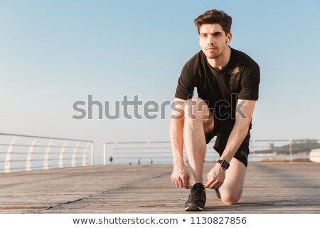 Handsome young sports man standing on the beach listening music with earphones. Stock photo © deandrobot