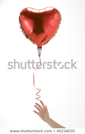 hand letting go of heart shaped balloon stock photo © monkey_business