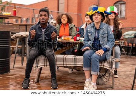 Young intercultural couple and their friends watching match broadcast Stock photo © pressmaster
