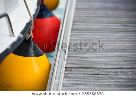 Fender buoys on sailboat side with ropes Stock photo © boggy