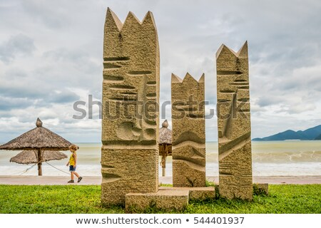 Beach in bad weather. Emptiness, high waves, parasols made of natural materials, statues and boy Stock photo © galitskaya