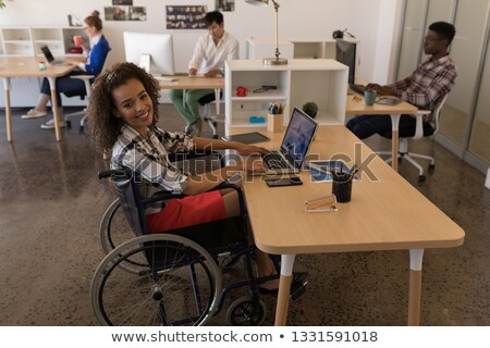 Side view of young disabled mixed-race female executive using laptop at desk in modern office Stock photo © wavebreak_media