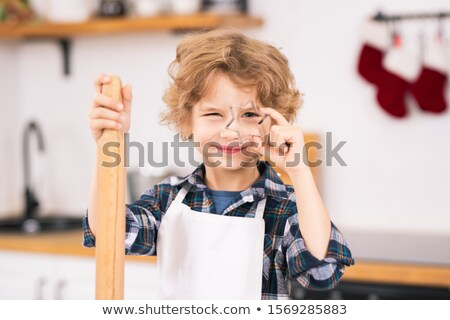 Adorable blond little boy in apron holding star shaped cutter and rolling-pin Stock photo © pressmaster
