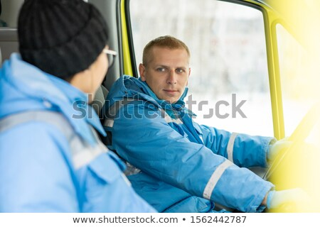 Сток-фото: Young Driver Of Ambulance Car Talking To Female Paramedic And Steering