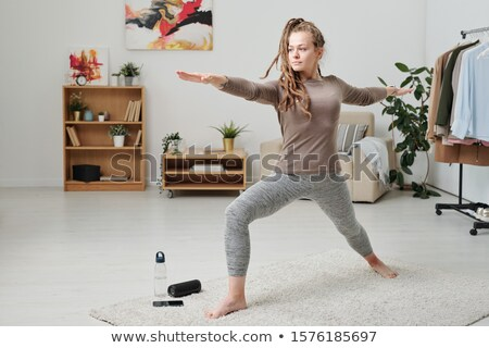 Pretty girl in activewear stretching legs and arms while working out on carpet Stock photo © pressmaster