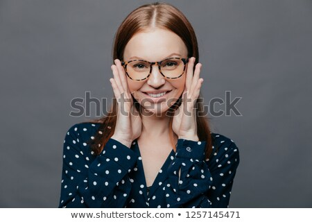 Photo of attractive woman with pleased facial expression, keeps both hands near cheeks, wears polka  Stock photo © vkstudio