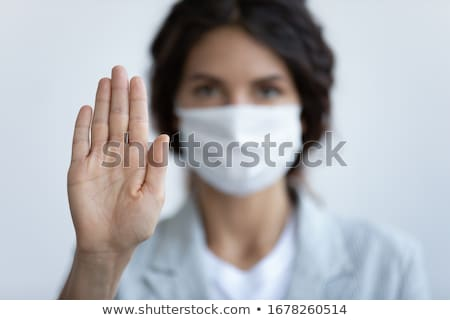 Young girl wearing medical face mask showing stop hand gesture for stop corona virus outbreak on the Stock photo © Len44ik