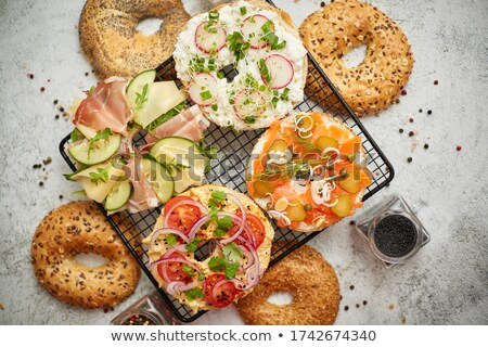 Delicious Bagel sandwiches with creamy cheese, ham, hummus, salmon and vegetables Stock photo © dash