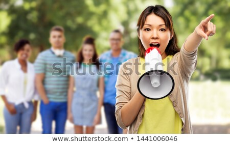 asian woman with megaphone over group of people Stock photo © dolgachov