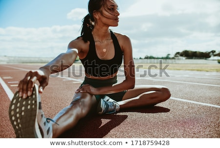 Stock photo: Woman athlete fitness stretch on athletics track