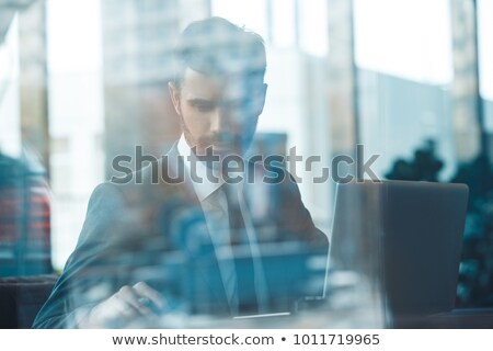 Businessman using a laptop outside a glass building Stock photo © photography33