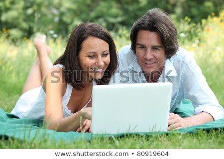 couple lying on the grass looking at a laptop computer screen stock photo © photography33
