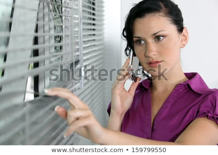 A brunette businesswoman peeping through the blinds. Stock photo © photography33