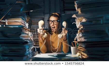 Stressed secretary answering two telephones Stock photo © photography33