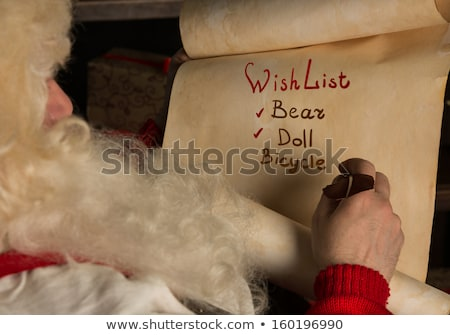 santa claus sitting at home and writing on old paper roll to do stock photo © hasloo