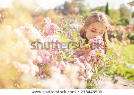 Pretty lady smelling the flowers Stock photo © konradbak