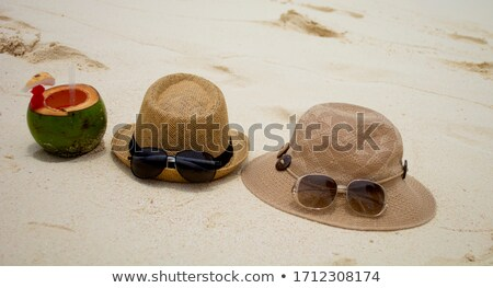 hat and sunglasses with two coco nut cocktails on  beach Stock photo © feedough