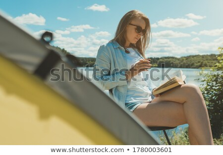 Woman reading a book at campsite Stock photo © bmonteny