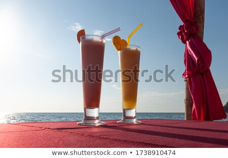 Red fruit icy cocktail in beach sand Stock photo © dariazu