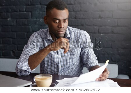 African man sitting at the table and signing document in office Stock photo © deandrobot