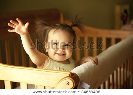 Baby girl standing on crib Stock photo © nyul