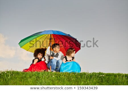hiding under a colorful umbrella stock photo © igabriela