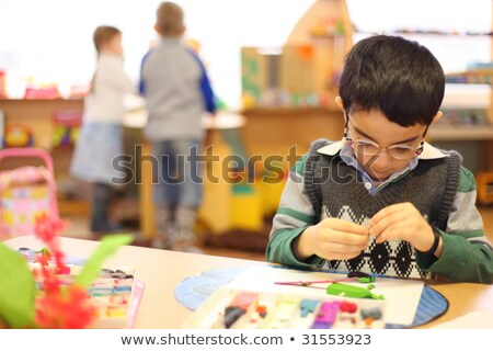 Boy in glasses moulds from plasticine on table in kindergarten Stock photo © Paha_L