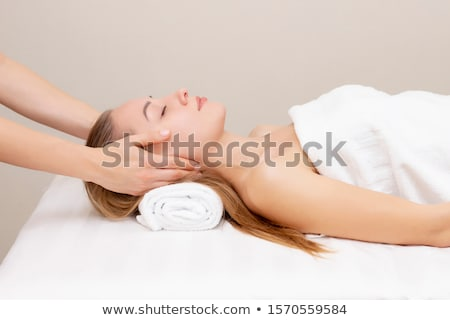 Portrait of a young woman getting spa treatment. Face massage Stock photo © dashapetrenko