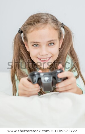Little girl lying playing with a game controller Stock photo © Giulio_Fornasar