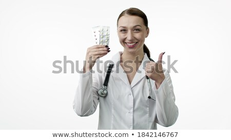 Woman nurse in lab coat showing pills and thumb up isolated Stock photo © deandrobot