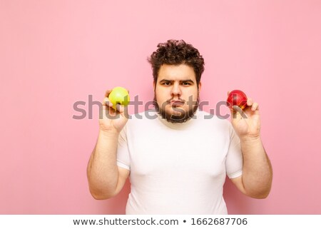 man standing on scale and holding apple in hand stock photo © rastudio