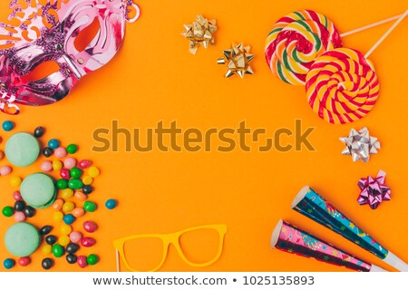 flat lay with sweets lollipops and party objects isolated on orange purim holiday concept stock photo © lightfieldstudios