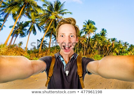 Tourist with smart phone in front of palm trees on beach Stock photo © Kzenon