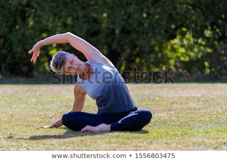 Senior woman doing yoga and legs stretching  in the park stock photo © boggy