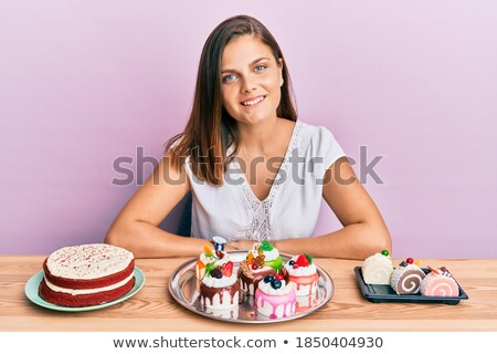 Portrait of a delighted young woman showing pastry Stock photo © deandrobot