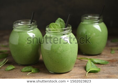 Blended green smoothie with ingredients on black table. stock photo © Illia