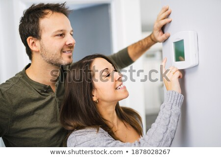 Couple set the thermostat at home Stock photo © Lopolo