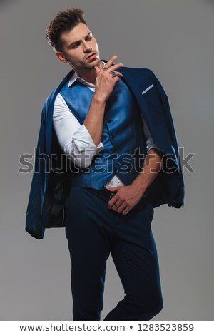 arrogant young man wearing blue suit looks down to side Stock photo © feedough