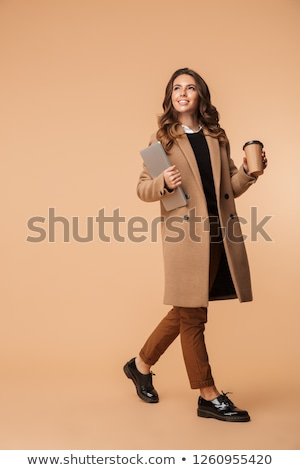 Photo of beautiful woman 20s smiling and holding takeaway coffee Stock photo © deandrobot