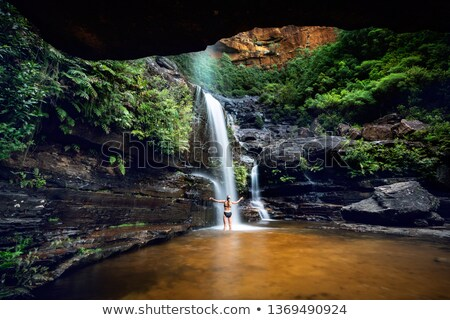 Woman cooling off in a mountain oasis and waterfall Stock fotó © lovleah