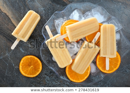 fruit ice cream on stick with slices fruits on black slate stock photo © manaemedia